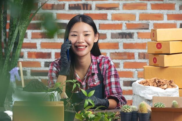 Verkauf von pflanzen online; frau lächelt, während sie auf dem handy spricht