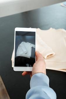 Verkaufen sie online im internet-e-commerce-geschäft frau, die ein foto von kleidung auf dem smartphone-verkauf macht