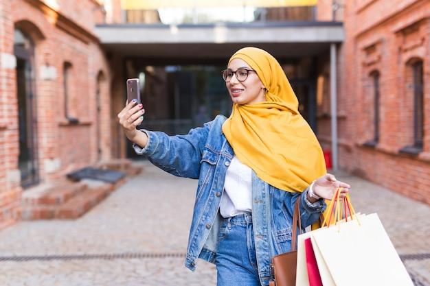 Verkaufs-, technologie- und kaufkonzept - glückliche arabische muslimische frau, die selfie im freien nach nimmt