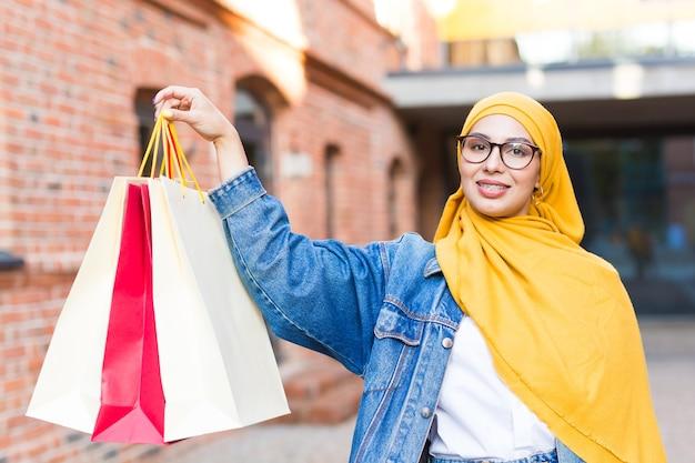 Verkaufs- und kaufkonzept - glückliches arabisches muslimisches mädchen mit einkaufstüten nach einkaufszentrum