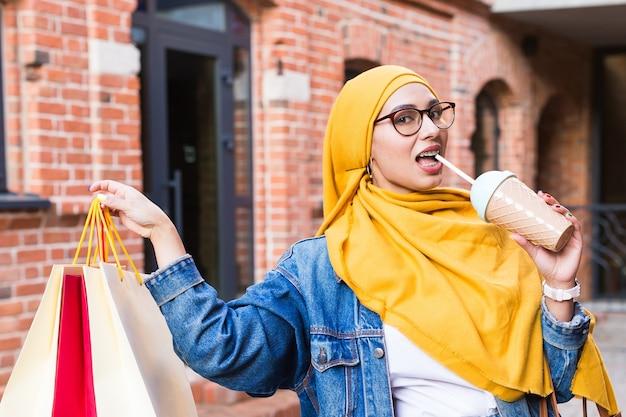 Verkaufs- und kaufkonzept - hübsches arabisches muslimisches mädchen mit einkaufstüten nach einkaufszentrum