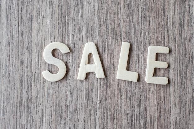 Verkaufs-wort von buchstaben des hölzernen alphabetes. geschäfts- und ideenkonzept