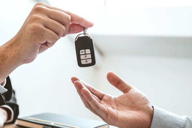 Verkaufsagent, der dem kunden autoschlüssel gibt und vereinbarungsvertrag, versicherungsauto unterzeichnet.