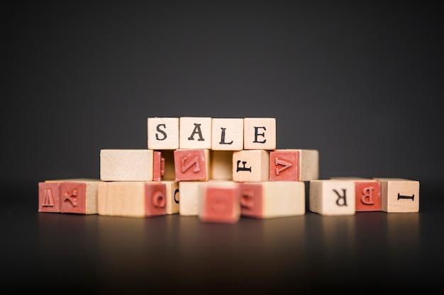 Verkaufsaufschrift auf holzklötzen auf tabelle