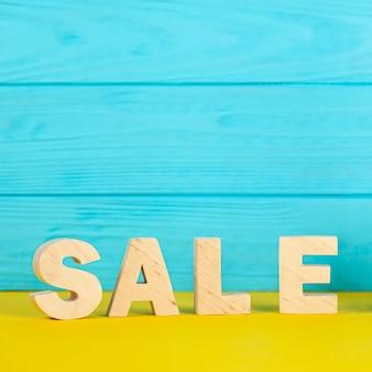 Verkaufsbeschriftung auf blauem hölzernem hintergrund
