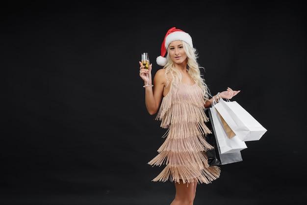 Verkaufskonzept. frau im luxuskleid und in der weihnachtsmannmütze, die weihnachten feiert