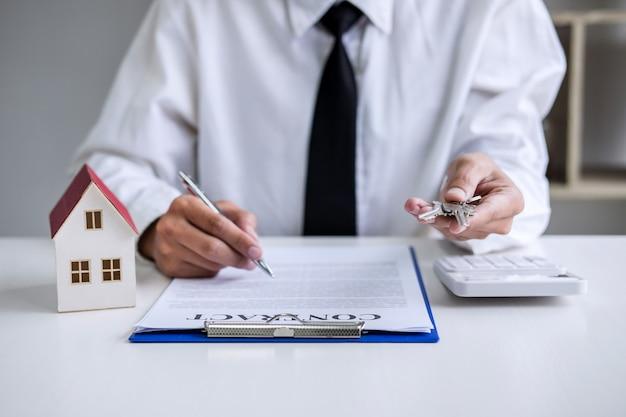 Verkaufsleiter, der dem kunden archivierungsschlüssel hält, nachdem mietpachtvertrag unterzeichnet worden ist