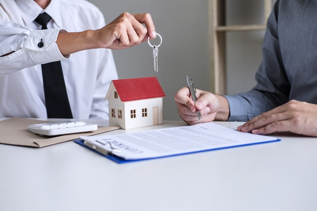 Verkaufsleiter, der dem kunden schlüssel gibt, nachdem mietpachtvertrag des verkaufskaufvertrages unterzeichnet worden ist