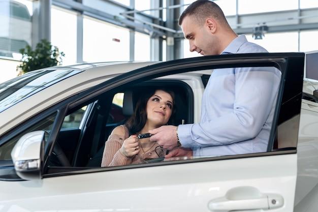 Verkaufsleiter, der schlüssel vom auto zum kunden gibt