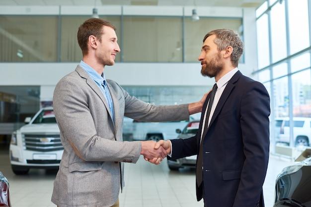 Verkaufsleiter händeschütteln mit dem kunden, der auto kauft