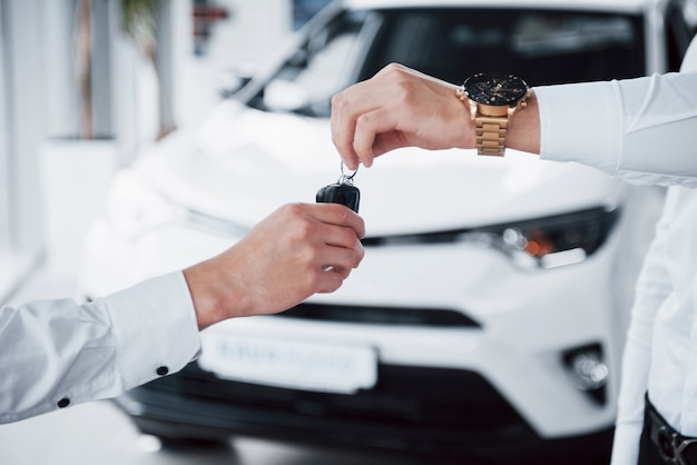 Verkaufsleiter im anzug, der das auto an den kunden verkauft.