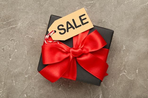 Verkaufspreisschild auf schwarzem geschenk auf grauem betontisch