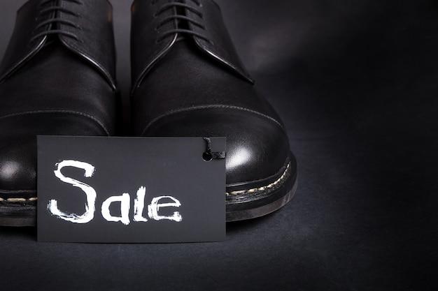 Verkaufsschild. schwarze oxford-schuhe auf schwarzem hintergrund. rückansicht. kopieren sie platz.