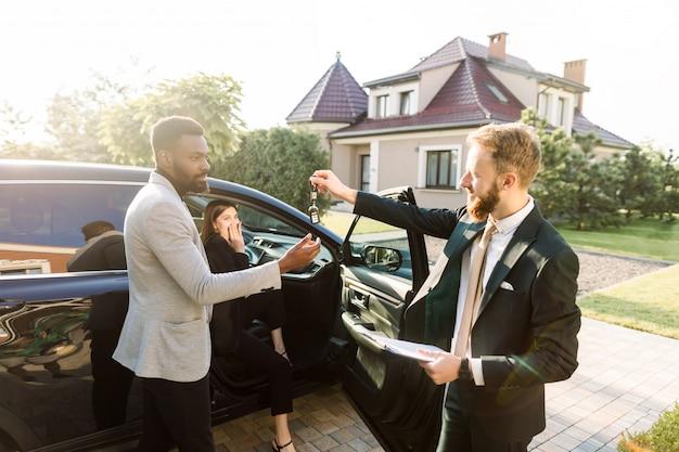 Verkaufssituation in einem autohaus im freien. der junge afrikaner bekommt den schlüssel für das neue auto vom kaukasischen verkaufsleiter. aufgeregte fröhliche frau sitzt glücklich im auto