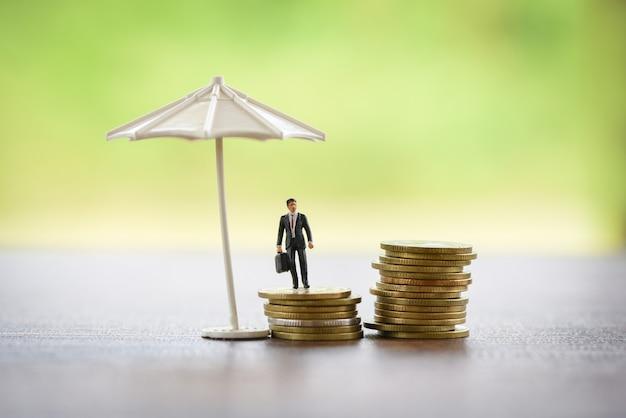 Verkaufsversicherungsvertragskonzept geschäftsmann, der schützende münze des aktenkoffers und des regenschirmes hält