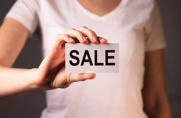 Verkaufswort auf papier in weiblichen händen