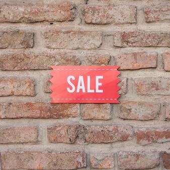Verkaufszeichen auf backsteinmauer