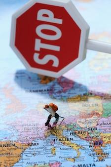 Verkehrsbeschränkungen. tourismus ist verboten. konzept der quarantäne in europa. koronavirus-epidemie. stoppschild und touristenfigur auf einer weltkarte. das tourismusverbot in der europäischen union
