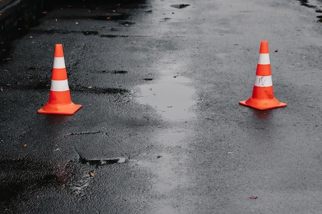 Verkehrskegel, mit weißen und orangefarbenen streifen auf grauem asphalt