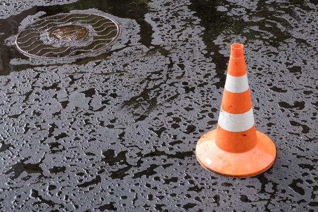 Verkehrskegel und ein mannloch auf neuem nassem asphalt
