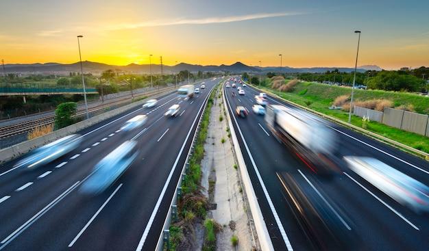 Verkehrsreiche landstraße bei sonnenuntergang, kommende und gehende fahrzeuge, stadtdruck