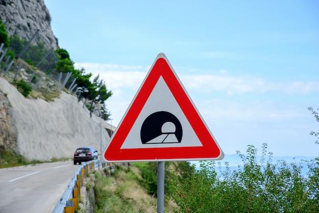 Verkehrsschild, das einen tunnel in den bergen ankündigt