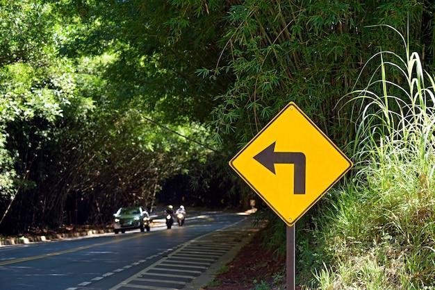 Verkehrsschild, das linke kurve warnt