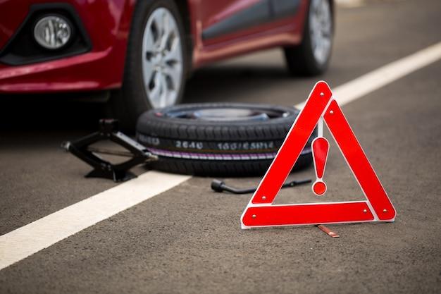 Verkehrsschild mit einem kaputten auto, reserverad und werkzeugen