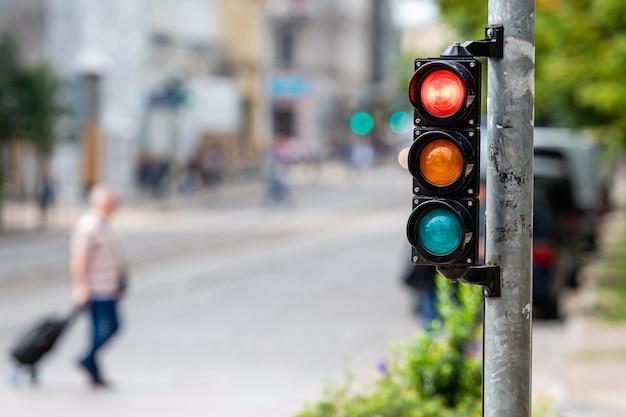 Verkehrssteuerungssemaphor mit rotem licht auf einem defokussierten stadthintergrund