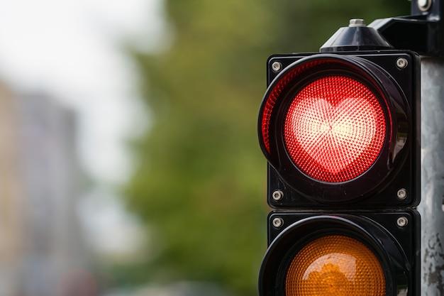 Verkehrssteuerungssemaphor mit roter herzform im semaphor auf einer defokussierten stadtoberfläche, valentinstagkonzept