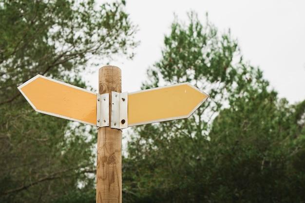 Verkehrszeichen auf einer straße im wald. gelbe wanderwegschilder