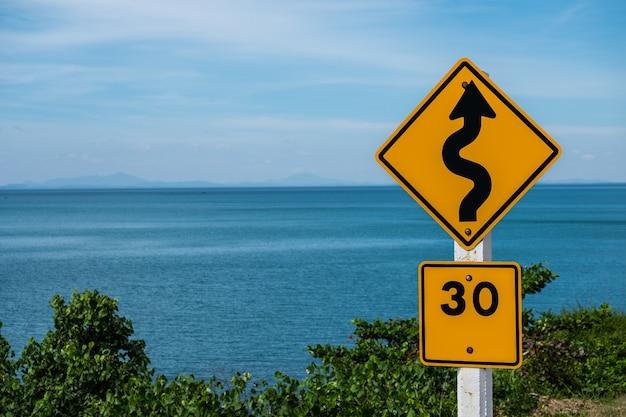 Verkehrszeichen, das eine kurvenreiche straße anzeigt, die geschwindigkeit zu 30 kilometern pro stunde begrenzt.