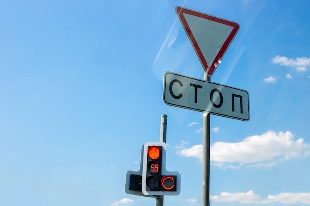Verkehrszeichen geben nach, stop-stop, elektronische ampel mit countdown, gegen den blauen himmel mit reflexion