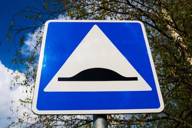 Verkehrszeichen-geschwindigkeitsschwelle. blaues quadrat mit weißem dreieck und schwarzem hindernis. foto in hoher qualität