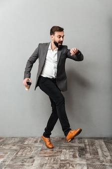 Verklemmter mann in voller länge mit dem mitnehmerkaffee, der die uhr spät betrachtet und entlang grau läuft