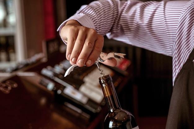 Verkorken eines teuren rotweinkorken, der einen jungen barkeeper hält, der in einer weinbar steht.