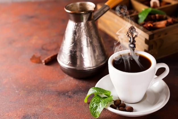 Verkostung einer tasse kaffee, kupfer türke und eine holzkiste mit gewürzen und verschiedenen gerösteten kaffeebohnen