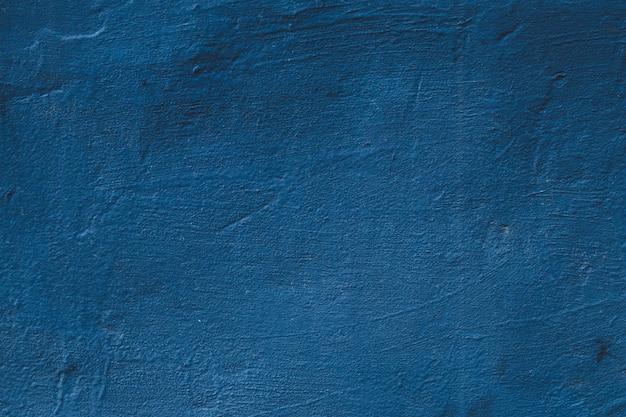 Verkratzte betonwand. blauer schmutzhintergrund, abstraktes muster, natürlich gemalte zementbeschaffenheit, dunkle steinschablone.