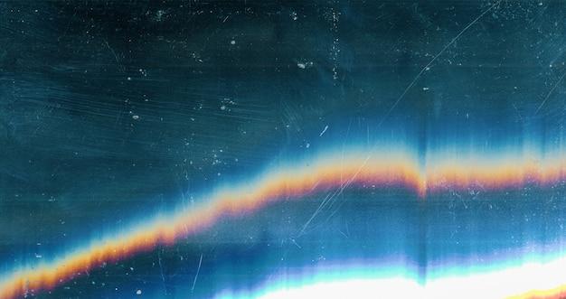 Verkratzte überlagerung. beschädigter laptop-bildschirm. blau verwittertes verblasstes glas mit verschmierten schmutzflecken staubpartikeln bunter regenbogenlinsen-flare-effekt.