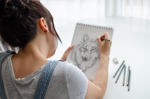 Verkürzung einer frau, die zu hause einen wolf in einen skizzenblock zeichnet. nahaufnahme