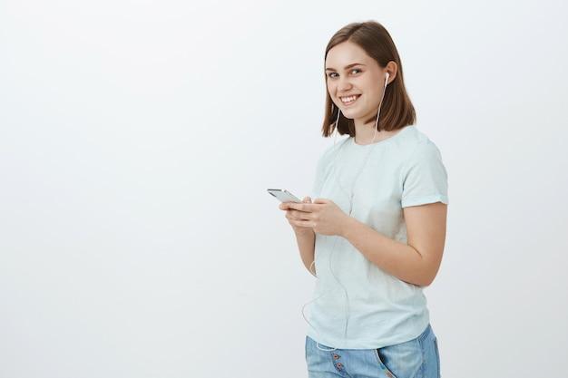 Verlasse dein zuhause niemals ohne musik. porträt der bezaubernden freundlich aussehenden entzückten jungen frau im lässigen outfit, das bereit ist, zur universität zu gehen, kopfhörer tragend und smartphone lächelnd beiseite haltend