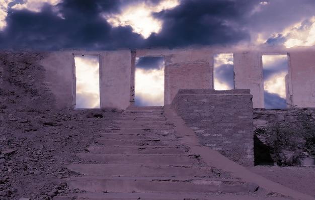 Verlassene alte große steinmauer mit einer treppe auf einem felsen unter einem dramatischen bewölkten himmel