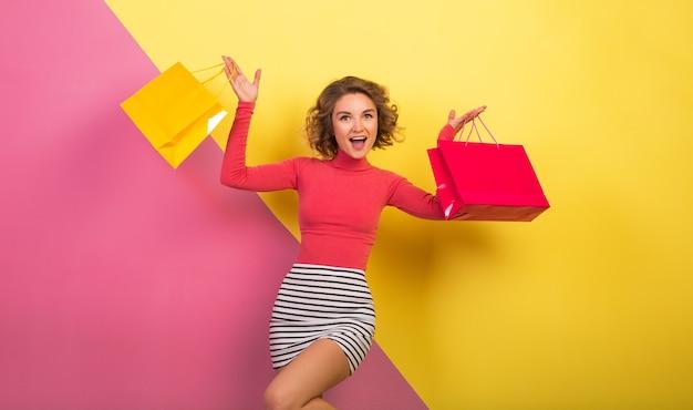 Verlassene attraktive frau im stilvollen bunten outfit, das einkaufstaschen mit glücklichem gesichtsausdruck, wehendem haar, rosa gelbem hintergrund, polohals, gestreiftem minirock, verkauf, discout, shopaholic hält