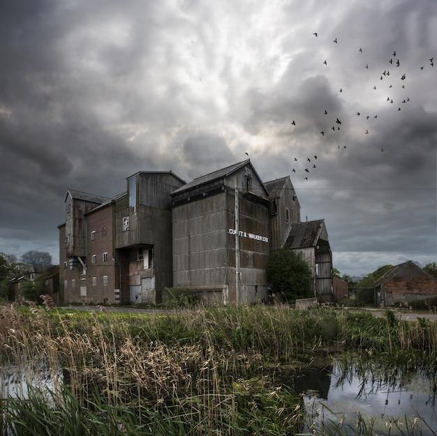 Verlassene mühle mit einem dunklen himmel und vögeln, die in north norfolk, großbritannien fliegen