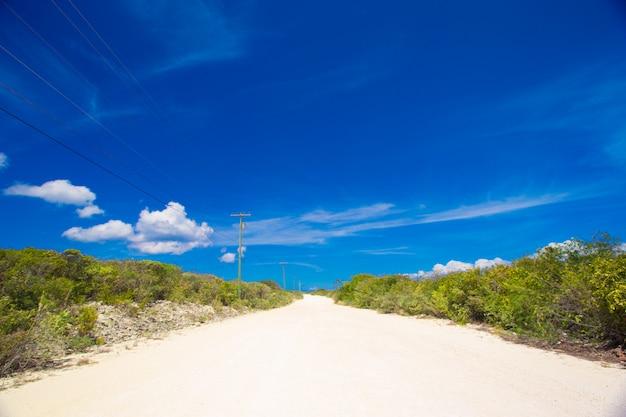 Verlassene tropische straße mit weißem sand auf karibikinsel