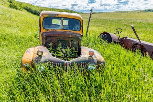 Verlassener antiker gelber lkw und traktor im hohen gras