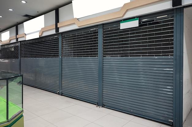 Verlassener geschlossener rollladenladen im kaufhaus aus wirtschaftlicher lage