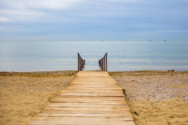 Verlassener strand in leerem teich, alte hölzerne mole über schmutzigem strandsand