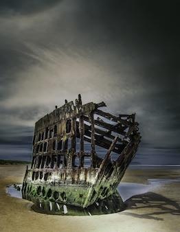Verlassenes boot am strand unter den atemberaubenden wolken