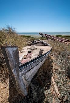 Verlassenes boot auf der vegetation auf den sanddünen von ria formosa-marschländern gelegen in der algarve, portugal.